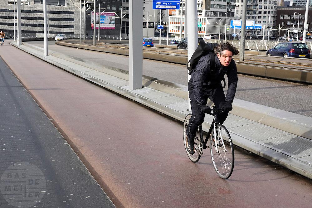 In Rotterdam rijden fietsers tegen de wind in de Erasmusbrug omhoog.<br /> <br /> In Rotterdam cyclists are riding the Erasmus bridge with a severe head wind.