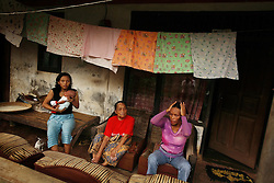 Zaenab Olis, 36, and her mother Mak Olis, 74, a retired traditional birthing attendant, sit on their porch outside Jakarta, Indonesia, April 19, 2006. Zaenab's 15-year-old daughter Titin sits with them. Mak performed a stomach massage on Zaenab, intentionally causing severe bleeding and the termination of her pregnancy. Over two million abortions are performed in Indonesia every year, many by unskilled practitioners. Thousands of women survive but often with life-long disabilities. It is said by doctors and activists that a woman dies every hour in Indonesia due to unsafe abortions.