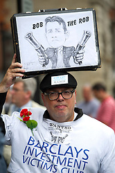 © London News Pictures. 04/07/2012. London, UK. A protestor holding up a caricature of BOB DIAMOND, the former CEO of Barclays Bank outside Portcullis House in London on July 4,2012 as BOB DIAMOND gives evidence to the Treasury Select Committee. BOB DIAMOND quit his role as Chief Executive of Barclays Bank following an interest rate-setting scandal that led to £290m in fines against the bank.  Photo credit: Ben Cawthra/LNP.