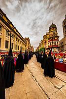 Hooded Penitents (Nazarenos) in the procession of the Brotherhood (Hermandad) San Bernardo,  on Avenue de la Constitucion (with the rounded Adriatic Building (Edificio de la Adriatica) behind, Holy Week (Semana Santa), Seville, Andalusia, Spain.