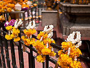 11 JULY 2011 - BANGKOK, THAILAND:   Flower garlands left on the fence around the Erawan Shrine in Bangkok. The Erawan Shrine (in Thai San Phra Phrom) is a Hindu shrine in Bangkok, Thailand that houses a statue of Phra Phrom, the Thai representation of the Hindu creation god Brahma. A popular tourist attraction, it often features performances by resident Thai dance troupes, who are hired by worshippers in return for seeing their prayers at the shrine answered. On 21 March 2006, a man vandalised the shrine and was subsequently killed by bystanders. The shrine is located by the Grand Hyatt Erawan Hotel, at the Ratchaprasong intersection of Ratchadamri Road in Pathum Wan district, Bangkok, Thailand. It is near the Bangkok Skytrain's Chitlom Station, which has an elevated walkway overlooking the shrine. The area has many shopping malls nearby, including Gaysorn, CentralWorld and Amarin Plaza. The Erawan Shrine was built in 1956 as part of the government-owned Erawan Hotel to eliminate the bad karma believed caused by laying the foundations on the wrong date..The hotel's construction was delayed by a series of mishaps, including cost overruns, injuries to laborers, and the loss of a shipload of Italian marble intended for the building. Furthermore, the Ratchaprasong Intersection had once been used to put criminals on public display. An astrologer advised building the shrine to counter the negative influences. The Brahma statue was designed and built by the Department of Fine Arts and enshrined on 9 November 1956. The hotel's construction thereafter proceeded without further incident. In 1987, the hotel was demolished and the site used for the Grand Hyatt Erawan Hotel.     PHOTO BY JACK KURTZ
