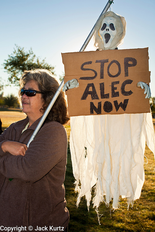 30 NOVEMBER 2011 - PHOENIX, AZ:    An anti-ALEC protester waits for a march to start in Phoenix Wednesday. About 300 people picketed the American Legislative Exchange Council (ALEC) conference at the Westin Kierland Resort and Spa in Phoenix, AZ, Wednesday. The protesters claim ALEC, a conservative think tank, violates its tax exempt status by engaging in lobbying, a charge ALEC officials deny. Many conservative pieces of legislation, like Arizona's anti-immigration bill SB1070, originate with ALEC conferences (SB 1070 originated at an ALEC conference several years ago). Many of the protesters are also members of the Occupy movement.     PHOTO BY JACK KURTZ