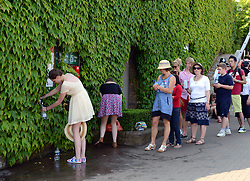 © London News Pictures. 07/07/2013 . London, UK. Members of the public queue to get drinking water as Andy Murray and Novak Djokovic of Serbia compete in the final of the Wimbledon Lawn Tennis Championships. Andy Murray won the match becoming the first British male to win the tournament in 77 years. Photo credit: Mike King/LNP