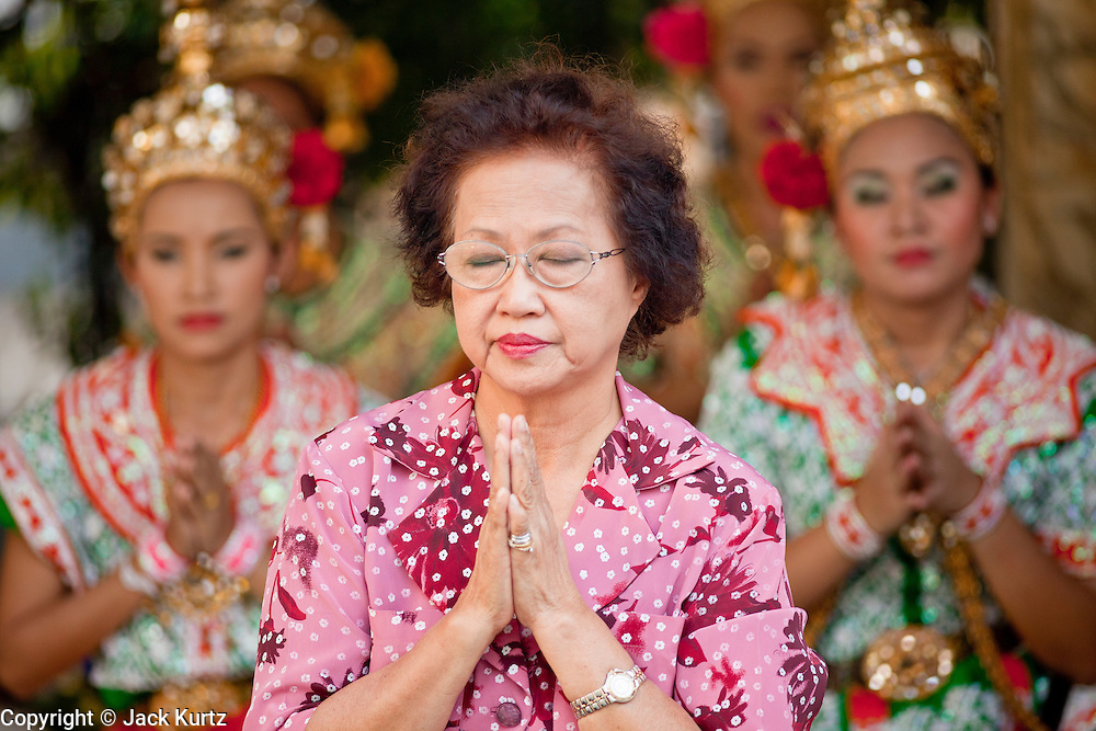 25 MARCH 2010 - BANGKOK, THAILAND: A woman prays while Thai classical dancers perform at the Erawan Shrine in Bangkok.  The Erawan Shrine (Thai: San Phra Phrom) is a Hindu shrine in Bangkok, Thailand that houses a statue of Phra Phrom, the Thai representation of the Hindu creation god Brahma. The Erawan Shrine was built in 1956 as part of the government-owned Erawan Hotel to eliminate the bad karma believed caused by laying the foundations on the wrong date. The hotel's construction was delayed by a series of mishaps, including cost overruns, injuries to laborers, and the loss of a shipload of Italian marble intended for the building. Furthermore, the Ratchaprasong Intersection had once been used to put criminals on public display. An astrologer advised building the shrine to counter the negative influences. The Brahma statue was designed and built by the Department of Fine Arts and enshrined on 9 November 1956. The hotel's construction thereafter proceeded without further incident.      PHOTO BY JACK KURTZ