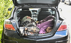 © Licensed to London News Pictures. 30/08/2020. City, UK. A person sleeps in the boot of a car in the village of Banwen in South Wales, during an illegal rave. The event, which was held in forestry above the village was attended by an estimated 3000 people from all over the UK. The government recently strengthened the laws to fine organisers of the illegal parties £10,000. Photo credit: Robert Melen/LNP