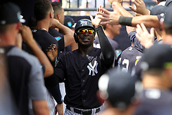 March 18, 2018 - Tampa, FL, U.S. - TAMPA, FL - MAR 18: Didi Gregorius (18) of the Yankees is congratulated on scoring by his team mates during the game between the Miami Marlins and the New York Yankees on March 18, 2018, at George M. Steinbrenner Field in Tampa, FL. (Photo by Cliff Welch/Icon Sportswire) (Credit Image: © Cliff Welch/Icon SMI via ZUMA Press)