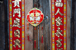 Chinese New Year decorations on very old wooden house  door in a Beijing hutong