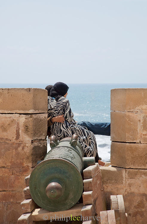 A young couple sit at the ramparts of the medina, overlooking the ocean in Essaouira, Morocco