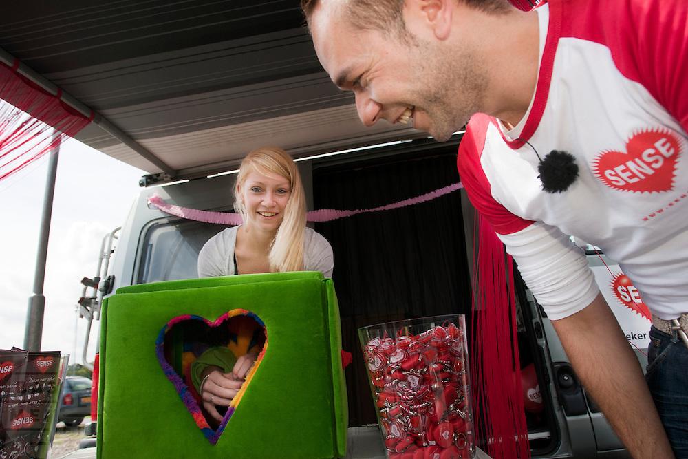 Onder toeziend oog van een medewerker van de GG&GD doet een meisje blindelings een neppenis een condoom om. Bij de busopstapplaats bij Muziekcentrum Vredenburg Leidche Rijn in Utrecht, ook wel de Rode Doos genoemd, deelt de GG&GD Utrecht condooms en informatiepakketten over veilig vrijen uit aan jongeren die met de bus op vakantie gaan. Met de actie hoopt de GG&GD het aantal SOA's te verminderen en jongeren bewust te maken van seksuele aandoeningen. Juist bij jongeren die op reis gaan, wordt vaak onveilig gevreeën.<br /> <br /> Youth going on a holiday are given free condoms and information about safe sex by the Dutch health organization.