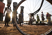 People gather to fetch water from a pond at Dikunani dam in Savelugu, northern Ghana, on Friday March 9, 2007. The only of four water sources that has not completely dried out around Savelugu, the pond is used by hundreds of people daily who sometimes walk several kilometers to fetch water. Despite the presence of mesh filters available to people who come get water, cases of guinea worm in the area have gone up sharply in the recent months.