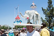 Brooklyn, NY - 18 June 2016. A spectator on Surf Avenue wears a huge tableau on his head, representing Coney Island's Elephant Hotel. The hotel, known as the Elephantine Colossus, was a tourist attraction on Coney Island from 1885 until it burned down in 1896.
