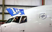 A member of the crew aboard a chartered Delta Boeing 767-300 carrying the Seattle Seahawks waves the 12th Man flag as it taxiied into a hangar at Newark Liberty International Airport at approximately 7:30pm EST on Sunday January 26, 2014 in Newark, N.J. (John Lok / The Seattle Times)