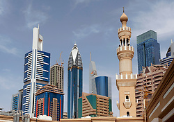 Skyline of financial district of  Dubai with mosque minaret contrasting with modern office towers, United Arab Emirates , UAE