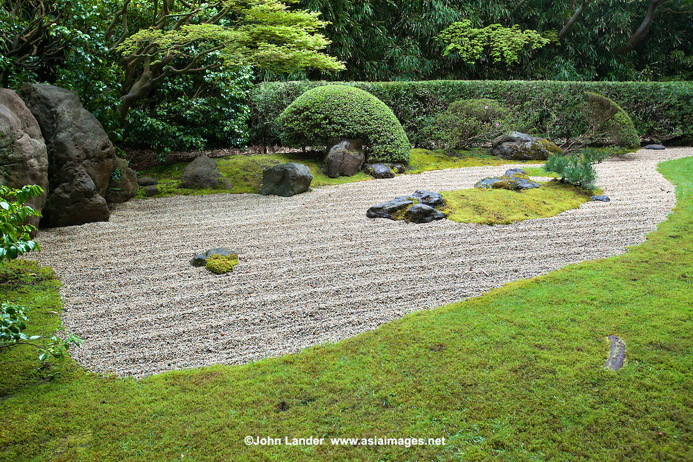"""The Zen Garden at the San Francisco Golden Gate Park Japanese Tea Garden was designed by Nago Sakurai, a leading Japanese landscape architect.  Dry landscape gardens, often called """"zen gardens"""" were introduced into Japan originally from China during the Kamakura Period.  Japanese Zen monks, during studies in China, were impressed with landscape scrolls and rock work in Chinese gardens.  So when they returned to Japan they adapted them and created what we think of today as a """"zen garden"""" or """"dry landscape garden"""".  The sand, gravel, stones are meant ro symbolize mountains, hills, islands, rivers, oceans and ponds."""