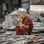 Mandalay is the monastic centre for Myanmar with several hundred thousand monks. Every child between 7 and 13 is expected to join a monastery for at least a few weeks. Here catching one at a break at a street bookshop.