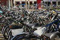 Bicycles locked up at a train station in Amsterdam. Bikes are everywhere in Amsterdam a centre of bicycle culture one of the most bike friendly large cities in the world.