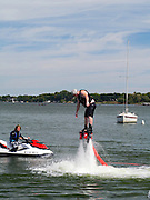 """A man """"flies"""" on a """"fly board,"""" with the help of a man on a jet ski; Lake Mendota, Madison, Wisconsin, USA"""