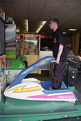 Young homeless man playing jet ski game in seaside arcade,