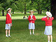 three school girls playing ball in the park, London, England