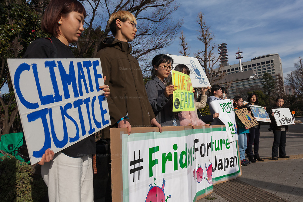 """A group of mostly young Japanese people point towards the government buildings as they take part in a demonstration as part of the """"Fridays for Future"""" movement outside the National Diet Building in Tokyo, Japan. Friday February 22nd 2019. Around 30 people took part in the demonstration in which started at 3pm. The Glbal Strike for Future was started by Swedish school student, Greta Thunberg who began striking from her school to demand adults do something about climate change to ensure the furture she was studying for. Since then thousands of strikes have taken place around the world. This was the first such strike in Japan and though no school students left their schools to take part the organisers hope the Global Strike for Future on March 15th will attract many young people in Japan"""
