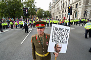 Meanwhile, Police continue to arrest climate change protestors in Parliament Square, central London on Tuesday, Sept 1, 2020 - Steve Branon an anti-Brexit campaigner is seen wearing Soviet Union Military outfit in an attempt to highlight Russian influence in the British Politics. He poses for VX Pictures with a background of the police lines. (VXP Photo/ Vudi Xhymshiti)