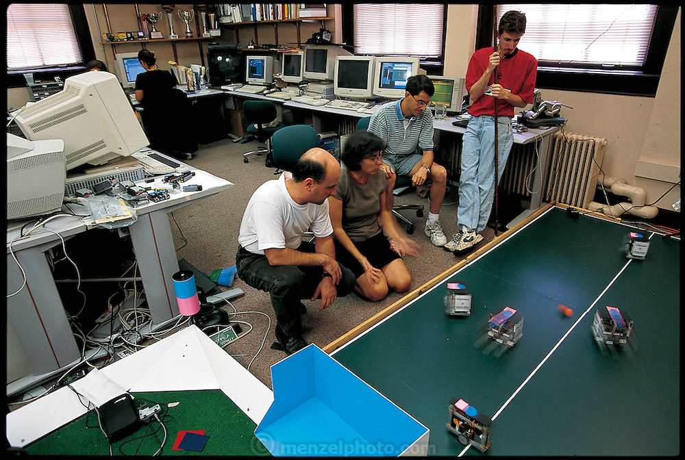 Reviewing the results of her work, Carnegie Mellon computer scientist Manuela Veloso (kneeling) watches the university soccer-robot team chase after the ball on a field on the floor of her lab. Every year, the Carnegie Mellon squad plays against other soccer-robot teams from around the world in an international competition known as RoboCup. Veloso's team, CMUnited, is highly regarded. Flanked by research engineer Sorin Achim, postdoctoral fellow Peter Stone, and graduate research assistant Michael Bowling (right to left), Veloso is running through the current year's strategy a month before the world championships in Stockholm. CMU's AIBO team members are Scott Lenser, Elly Winner, and James Bruce. Pittsburgh, PA. From the book Robo sapiens: Evolution of a New Species, page 214.