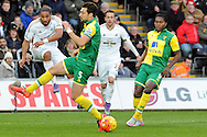 Swansea City captain Ashley Williams (l) shoots at goal challenged Norwich's Russell Martin (5).  Barclays Premier league match, Swansea city v Norwich city at the Liberty Stadium in Swansea, South Wales on Saturday 5th March 2016.<br /> pic by  Carl Robertson, Andrew Orchard sports photography.