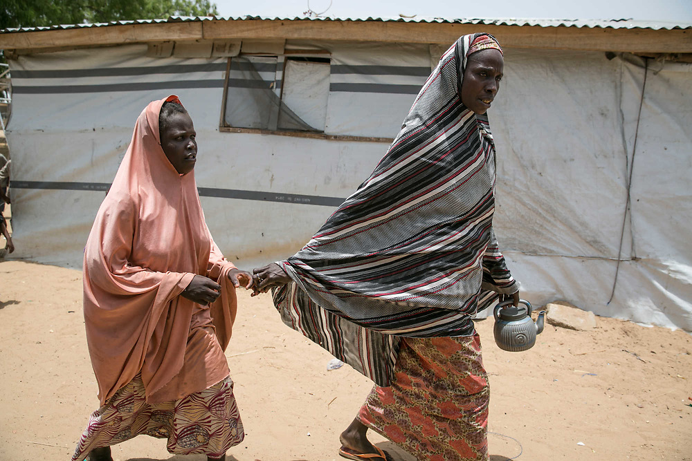 """Amina, 15, left, is escorted by her mother, Arfaya, at right, after the mother helped her use the toilet inside an IDP camp in Maiduguri, Nigeria, April 24, 2019. Amina, who was blind and forcibly married to another blind man inside a Boko Haram camp in 2015, was raped by an IDP man after she escaped and settled in an IDP camp in the outskirts of Maiduguri five days before this photo was taken. The man was arrested, but he was soon to be released by a bail. Amina said, """"I just want justice."""""""