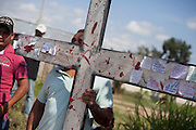 A man holds a cross in the representation on the Migrants Viacrucis in the streets  Tenosique, Tabasco, on March 29th 2013.  In the walk, that started in La Palma (32 km away from Tenosique), a hundred of migrants and human rights defenders walked demanding end on extortions. (Photo: Prometeo Lucero)