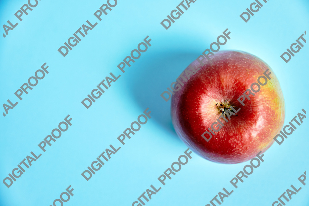 From above shot of ripe red apple lying on right side of blue background.