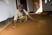 Indian woman cleaning the clay floor of her house. Coorg or Kadagu is the largest coffee growing region of India, in the state of Karnataka, the inhabitants - the Kodavas have been cultivating crops such as coffee, black pepper and cardamon for many generations.