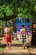 Rear view of two shirtless male tourists walking together, Little Corn Island, Nicaragua