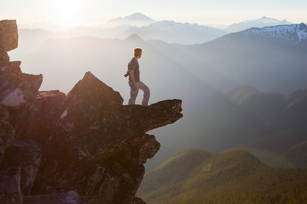 Stephen Byrne looks out over the Cascade River drainage and Mount Baker from the summit of Hidden Lake Peaks, North Cascades National Park, Washington.