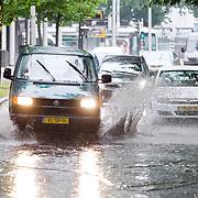 Foto: David Rozing Nederland Rotterdam 27 juli 2013 20130727 Noodweer in Nederland, zware onweersbuien teisteren Rotterdam. In korte tijd valt er een enorme hoeveelheid regenwater. Straat is onder gelopen en auto's banen zich een weg door het water. Waterballet. Foto: David Rozing