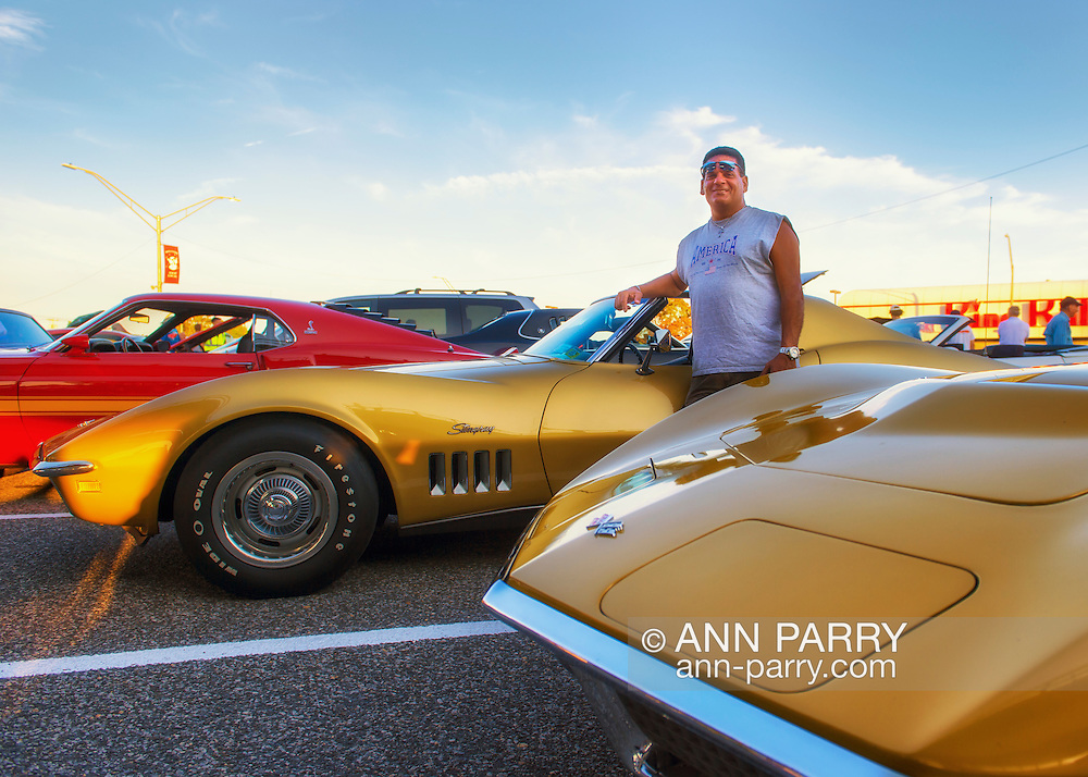 Bellmore, New York, USA. 7th August 2015. JIMMY STELLAS, of Freeport, is standing in front of his War Bonnet Yellow 1969 Corvette Stingray, at the Friday Night Car Show held at the Bellmore Long Island Railroad Station Parking Lot. Hundreds of classic, antique, and custom cars were on view at the free weekly show, sponsored by the Chamber of Commerce of the Bellmores. In front of Stellas is a Riverside Gold 1972 Stingray Vette.