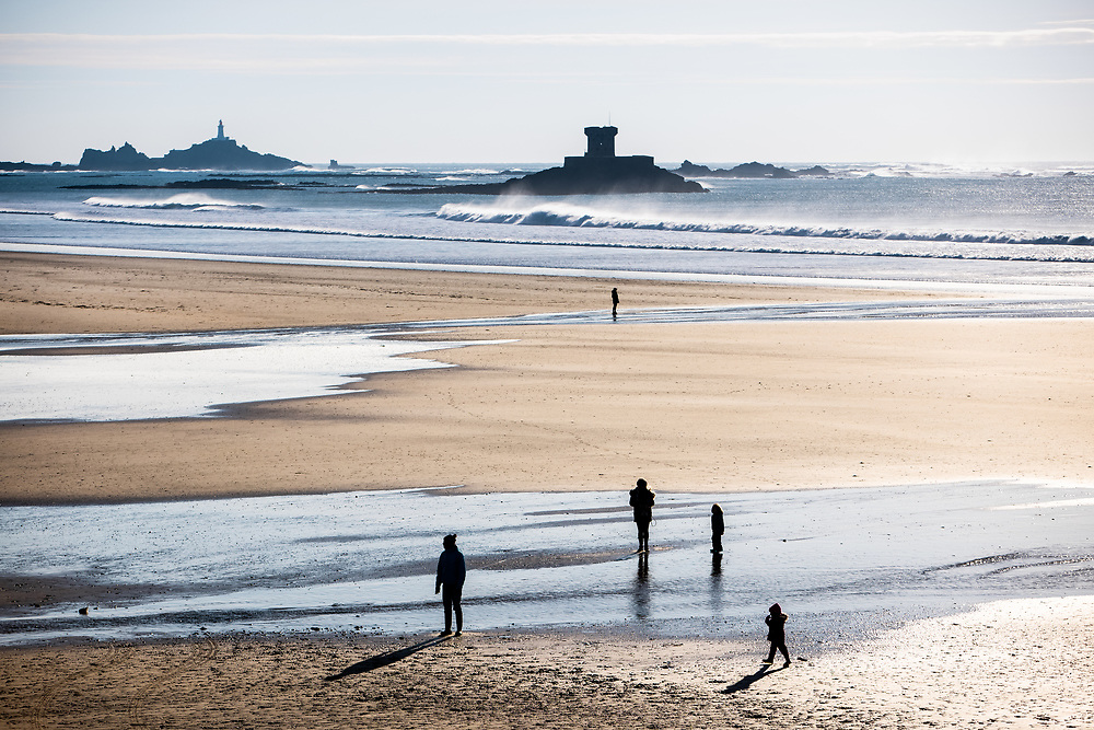 Family walking on the beach at St Ouen on a winter afternoon, with views out across the waves to La Rocco Tower and Corbiere lighthouse