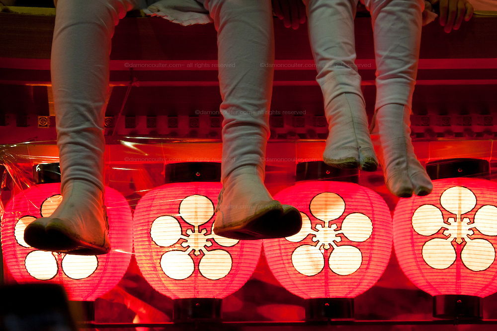 The legs of a man and child in traditional tabi sandals and legging sit on a danjiri float that is illuminated with red lanterns during the Kishiwada Danjiri matsuri. Kishiwada, Osaka, Japan Sunday, September 20th 2009. Ornately carved floats called Danjiri are pulled through the streets of Kishiwada during the danjiri festival or matsuri. Each float weigh about 4 tonnes and stands over 3 metres high. They are pulled by teams of up to a thousand people, young and old, and each challenges itself to skid the danjiri round street corners at great speed.