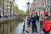 Nederland, Amsterdam, 26-4-2015Drukte op de Wallen. Op de oudezijds lopen drommen toeristen langs de sekswinkels en ramen met prostituees. Een jonge aziatische toerist maakt selfies aan de gracht.FOTO: FLIP FRANSSEN/ HOLLANDSE HOOGTE