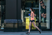 """A woman wearing a face protective mask run through """"Dolce and Gabbana"""" store street near Oxford Street in London on Thursday, May 28, 2020. The government in Britain eased restrictions across England as a slow loosening of the coronavirus lockdown gets underway, with people now encouraged to return to work if unable to do so from home and unlimited outdoor exercise now allowed. As the row over Prime Minister Boris Johnson's top aide Dominic Cummings' Durham trip, continues, the prime minister's populist appeal has been hammered by the news and members of the public who have seen the evidence and believe that PM Johnson's chief adviser Cummings flouted lockdown rules that the government had imposed on the rest of the country by driving 250 miles (400 kilometres) to his parents' house while he was falling ill with suspected COVID-19. (Photo/ Vudi Xhymshiti)"""