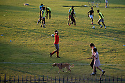 As other park-users walk their pet dog, young male footballers train in Ruskin Park a south London green space, during late afternoon, on 21st September 2021, in London, England.