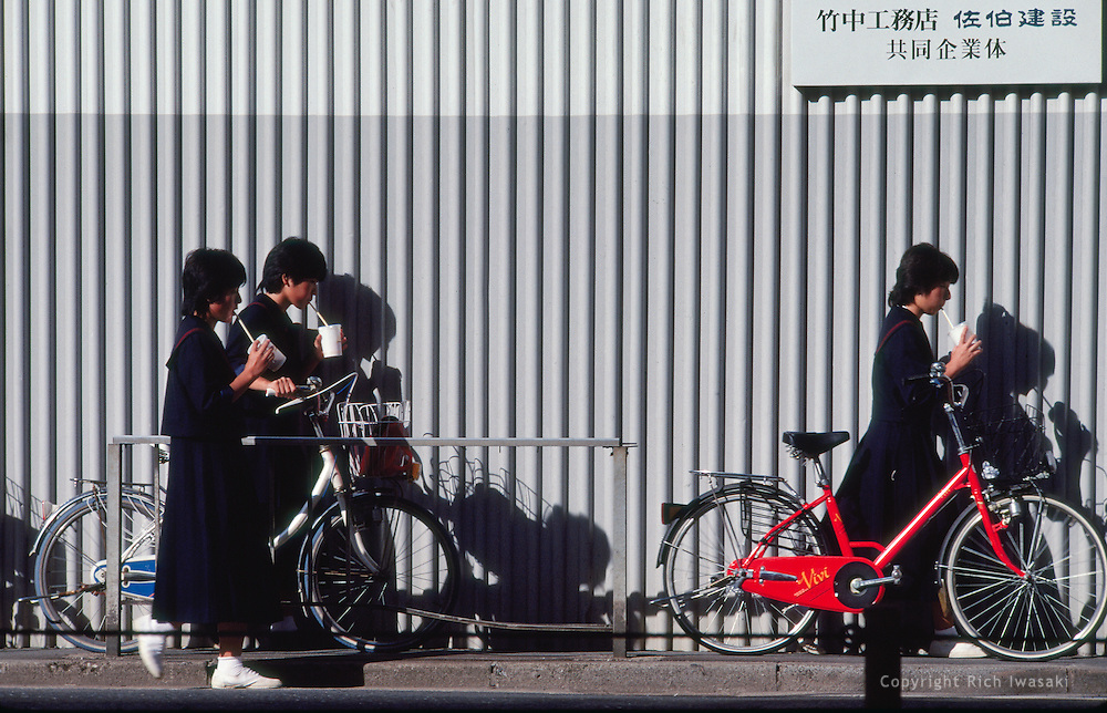School students walk with bicycles past metal wall while sipping drinks, Tokyo, Japan