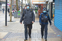© Licensed to London News Pictures 15/02/2021.        Bexleyheath, UK. Police officers wearing masks on patrol. Shoppers at the Broadway in Bexleyheath, South East London today during a third national coronavirus lockdown. Non-essential shops could open in weeks if the Covid-19 infection rate keeps dropping. Photo credit:Grant Falvey/LNP