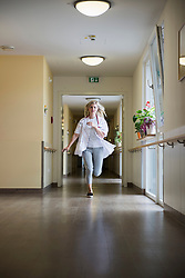Female doctor running down the hallway, Bavaria, Germany, Europe