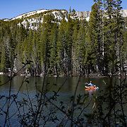 A slow start to summer in the Eastern Sierras as record snowfall carried over into the summer months. Fishermen enjoy the scenery while float tube fishing Lake Mamie with Crystal Crag in the background