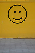 Smiley face motif on a yellow wall in London, England, United Kingdom. A smiley, sometimes called a happy face or smiley face, is a stylised representation of a smiling humanoid face that is a part of popular culture worldwide. The classic form designed by Harvey Ball in 1963 comprises a yellow circle with two black dots representing eyes and a black arc representing the mouth.