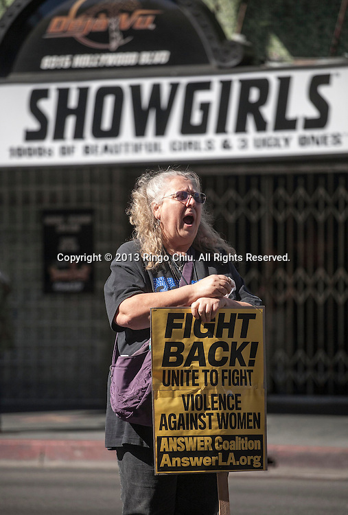 A protest shouts slogans in front of a showgirls bar during a march and rally ``calling on women to take to the streets to stop violence against women everywhere.'' as they march to commemorate the International Women's Day in Los Angeles, Saturday, March 9, 2013. (Photo by Ringo Chiu/PHOTOFORMULA.com).