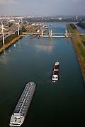Nederland, Zuid-Holland, Botlek, 19-09-2009; Functioneringssluiting Hartelkering, de waterkering in het Hartelkanaal  wordt een maal per jaar, voordat het stormseizoen begint, getest. Tijdens  het sluiten van de kering ligt alle scheepvaartverkeer naar de Rotterdamse haven stil. .Links in de achtergrond Botlek en olieraffinaderij, rechts Hoogvliet en Oude Maas. In de voorgrond wachtende binnenvaartschepen. Rechts de dijk die deel uit maakt van de Europoortkering..De kering sluit normaal gesproken alleen bij dreigende stromvloed en bij een waterstand van 3 meter of meer boven NAP. De kering, onderdeel van de Deltawerken, vormt samen met de Maeslantkering  de Europoortkering en beschermt Rotterdam en achterland bij extreme waterstanden. .Netherlands, Rotterdam harbour. Aerial view of one of the two storm surge barriers. This barrier, the Hartelkering  in the Hartel canal, together with the greater nearby  Maeslant barrier (in the New Waterwy), are tested during the so-called functioning closure, taking place one a year before the storm season begins. The waterway and canal, leading to the Port of Rotterdam, are closed during the test..luchtfoto (toeslag), aerial photo (additional fee required).foto/photo Siebe Swart.De kering sluit normaal gesproken alleen bij dreigende stromvloed en bij een waterstand van 3 meter of meer boven NAP. De kering, onderdeel van de Deltawerken, vormt samen met de Maeslantkering  de Europoortkering en beschermt Rotterdam en achterland bij extreme waterstanden. .Netherlands, Rotterdam harbour. Aerial view of one of the two storm surge barriers. This barrier, the Hartelkering  in the Hartel canal, together with the greater nearby  Maeslant barrier (in the New Waterwy), are tested during the so-called functioning closure, taking place one a year before the storm season begins. The waterway and canal, leading to the Port of Rotterdam, are closed during the test..luchtfoto (toeslag), aerial photo (additional fee required).foto/photo Siebe Swart