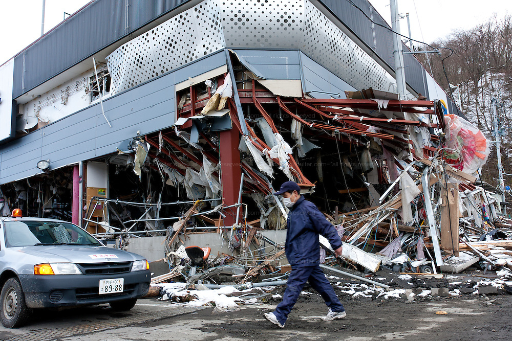 A man walks past the remains of a pachinko parlour after the tsunami that struck the north east coast of Japan on March 11th. Kamaishi, Iwate, Japan. March 17th 2011