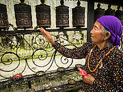 31 JULY 2015 - KATHMANDU, NEPAL: A woman spins prayer wheels around Swayambhunath Stupa, a large Buddhist stupa in Kathmandu. Parts of the stupa were badly damaged in the Nepal earthquake of 2015 but it is still open for religious devotees and tourists. Construction of the stupa started in the 1600s.    PHOTO BY JACK KURTZ