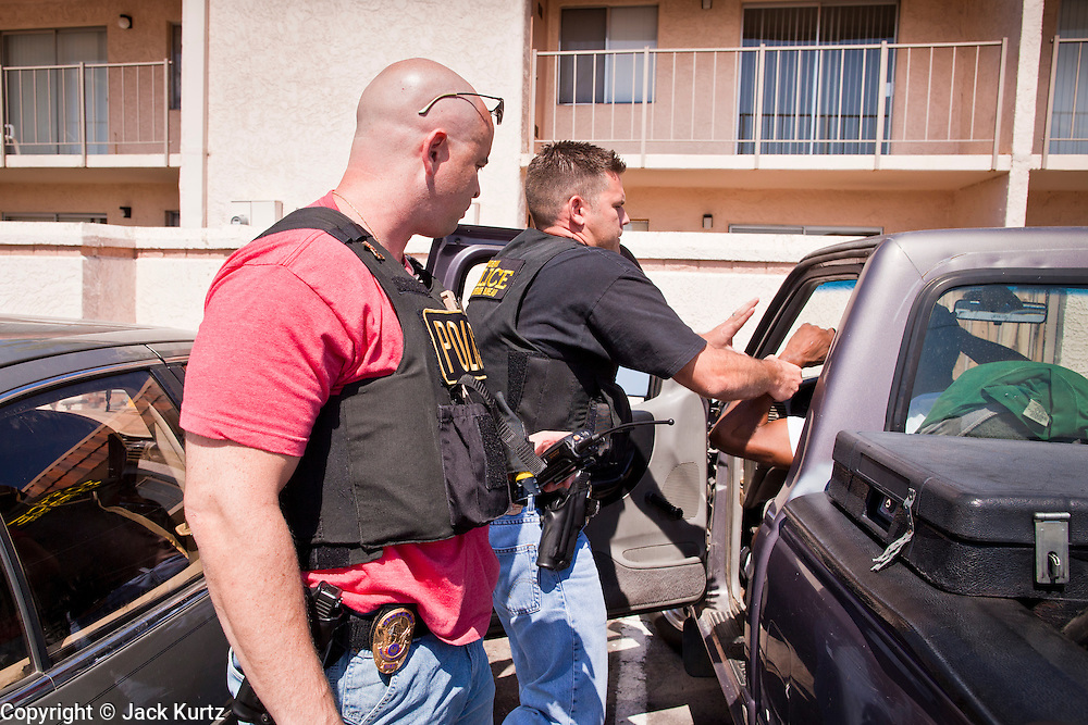 21 SEPTEMBER 2010 - PHOENIX, AZ:  Phoenix police Sgt. Doug McBride (CQ) and Detective Dave Dodd (CQ) control a man before arresting him on weapons and drug charges in central Phoenix Tuesday. Crime has steadily dropped in Phoenix over the past few years, in line with national trends. The latest number released this month showed Phoenix reported fewer 2010 homicides, rapes, robberies, thefts - in addition to other major crimes -- compared with the same time period the previous year. Detectives in the Phoenix police department's Major Offender Unit make several arrests every day.   PHOTO BY JACK KURTZ